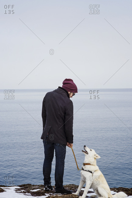 Man standing at water's edge with his loyal white dog