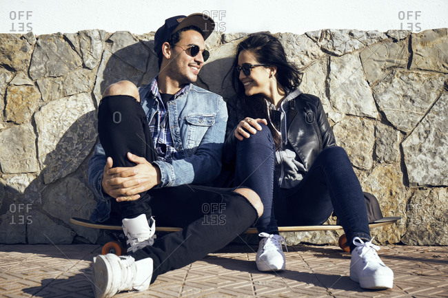 Couple sitting on a skateboard together