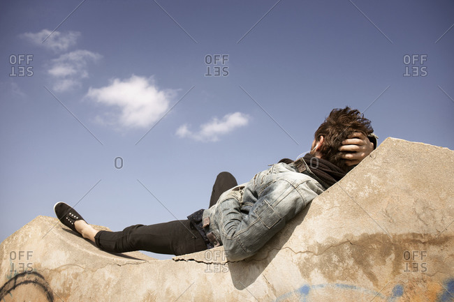 Young man relaxing on a large cement block