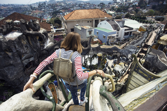 Dalat, Vietnam - March 16, 2016: Woman walking carefully down ornate rooftop of the Hang Nga Guesthouse