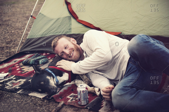 Man lying by a tent with a dog