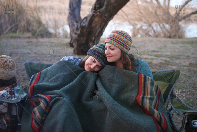 Two women cuddling on a camping trip