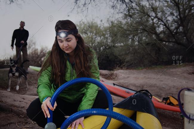 Woman inflating a kayak - Offset