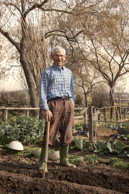 Portrait of an old man standing in his garden