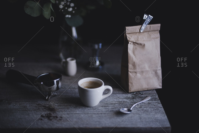 Coffee mug, espresso handle and paper bag on a rustic wooden table