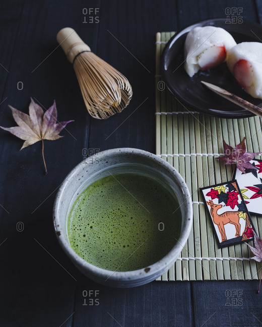 Green tea, Japanese maple leaves and sushi on a wooden table