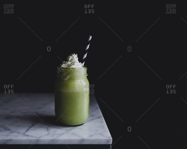 Blended green smoothie on a marble surface