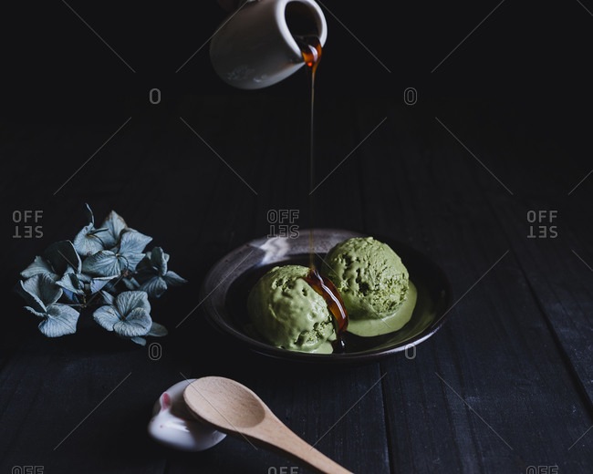 Sauce being poured over two scoops of green tea ice cream