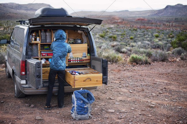 Woman packing gear from her vehicle to go hiking