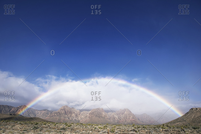Rainbow on a cloudy day over a mountain landscape