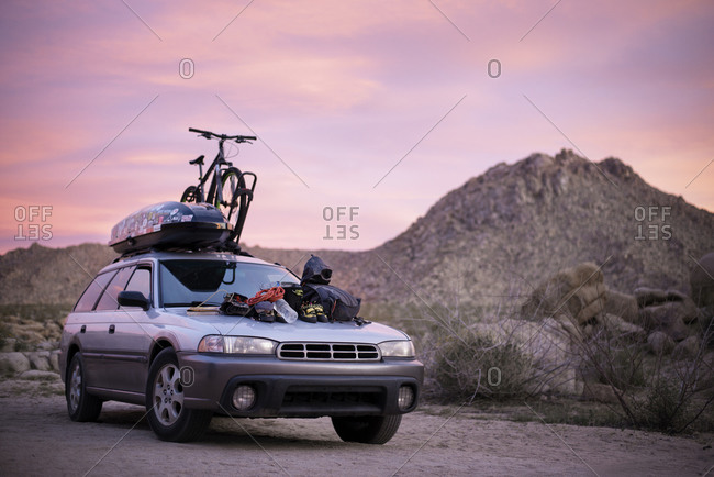 Joshua Tree, CA, USA - March 21, 2016: Car with mountain bike and climbing gear parked in desert at sunset