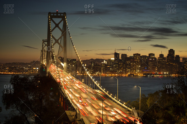 The Bay Bridge and city skyline illuminated at night, San Francisco, California