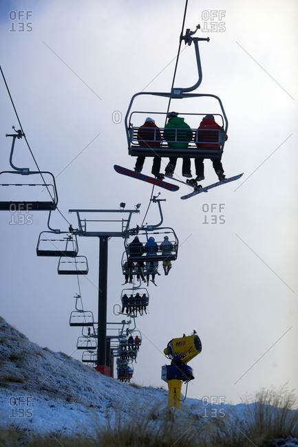 Skiers and snowboarders riding the ski lifts at Coronet Peak, Queenstown,  South Island, New Zealand