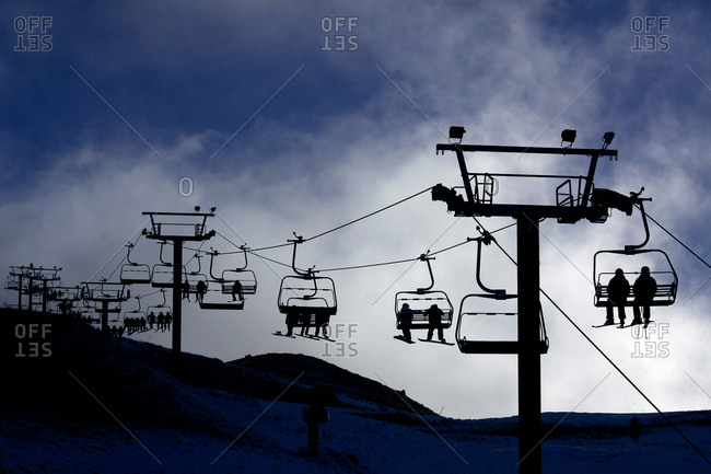 Silhouette of skiers and snowboarders riding the ski lifts at Coronet Peak, Queenstown,  South Island, New Zealand