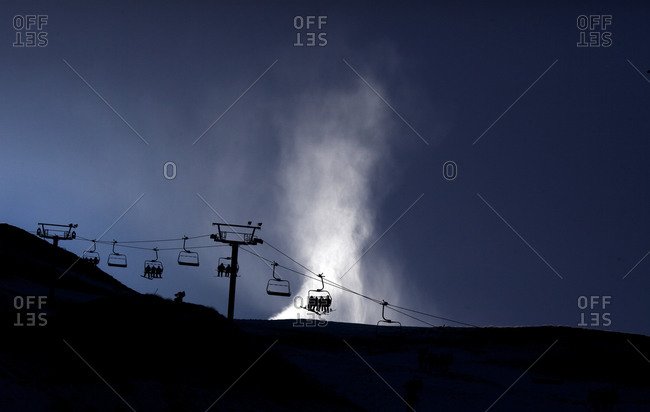 Silhouette of the ski lifts and a snow machine blowing snow at Coronet Peak, Queenstown,  South Island, New Zealand