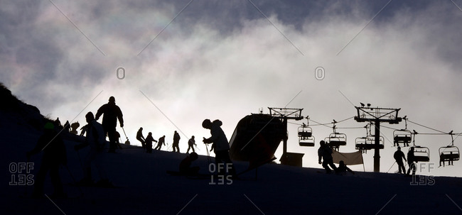 Silhouette of skiers and snowboarders by the ski lifts at Coronet Peak, Queenstown,  South Island, New Zealand
