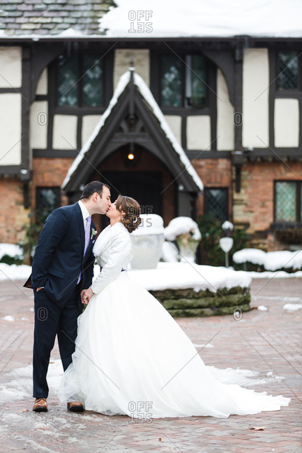 Bride and groom kissing in courtyard