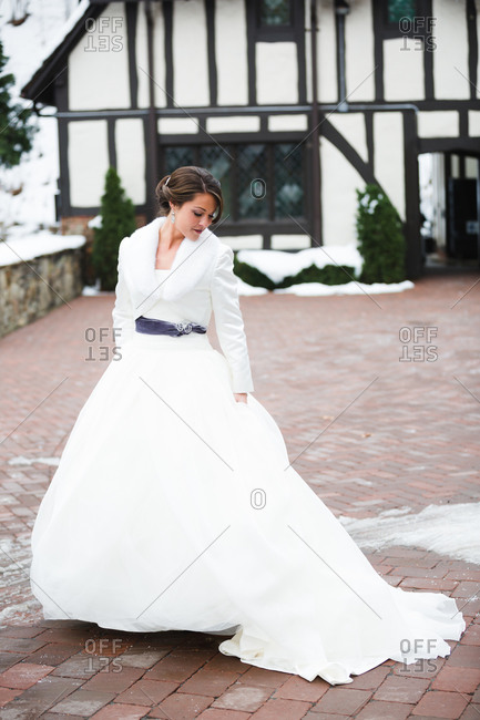 A bride in snowy courtyard