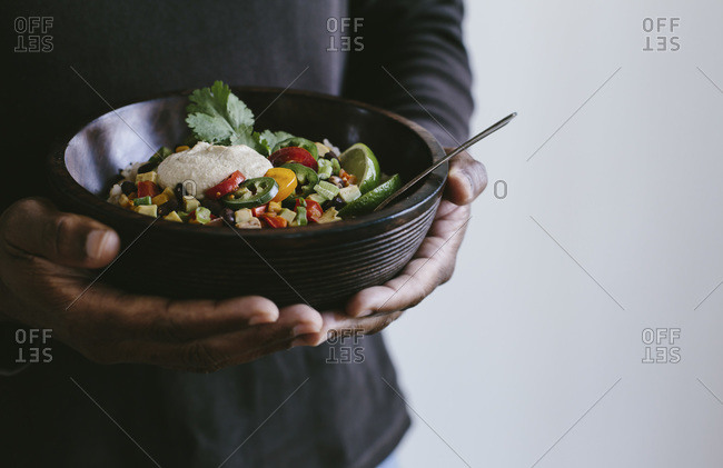 Man holding a Mexican burrito bowl topped with cashew chipotle cream sauce