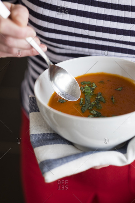 Person holding a bowl of tomato soup with fresh basil