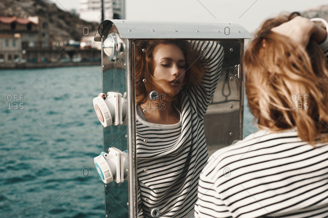 Woman standing on a pier looking at her reflection in a metal box