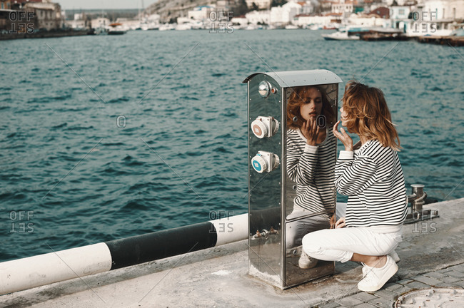Woman checking her makeup in the reflection of a metal box on a pier