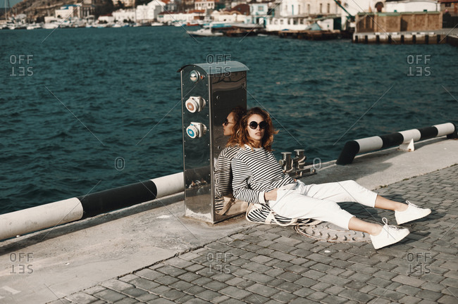 Woman resting against a metal box on a pier