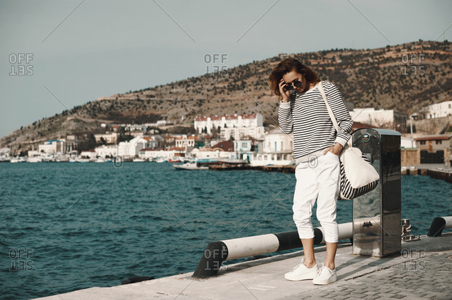 Woman standing on a pier in a seaside town