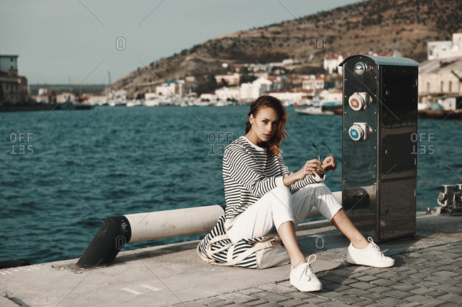 Woman sitting on a pier in a seaside town holding sunglasses