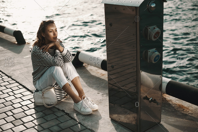 Woman resting on a pier near a shiny metal box