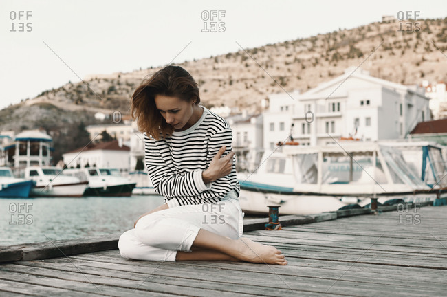 Woman sitting on a pier in a seaside village hugging herself