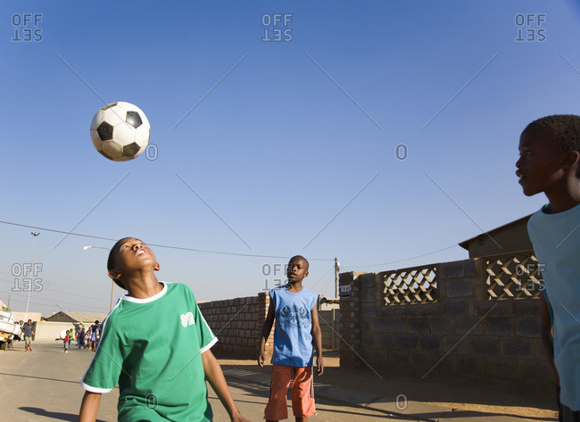 Boys playing soccer outside in the street