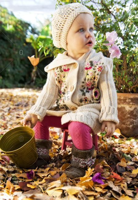 Girl sitting outside on a fall day surrounded by leaves