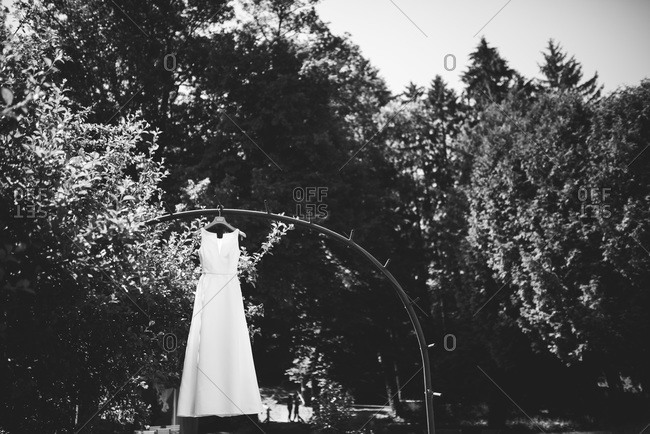 Wedding dress hanging outside in a natural area surrounded by trees