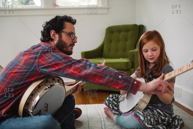 Man helping girl learn banjo