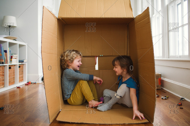 Brother and sister playing together inside a cardboard box on the floor