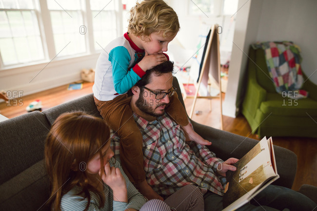 Father sitting on a couch reading a book to his son and daughter