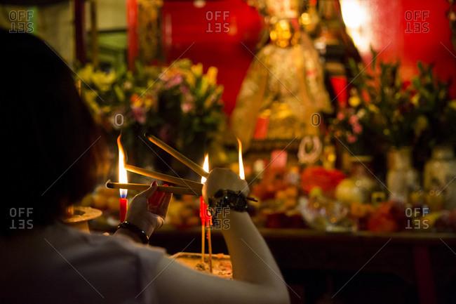 Woman lighting incense sticks at Man Mo temple, Hong Kong