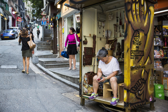 September 13, 2015: Woman listening to music on her small handicraft store in Hong Kong