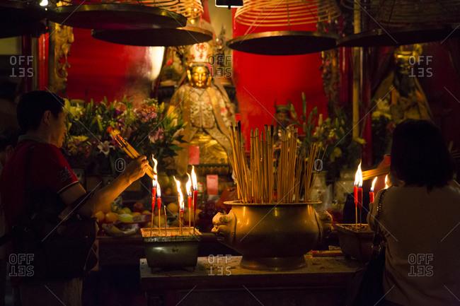 September 13, 2015: People lighting incense sticks at Man Mo temple, Hong Kong