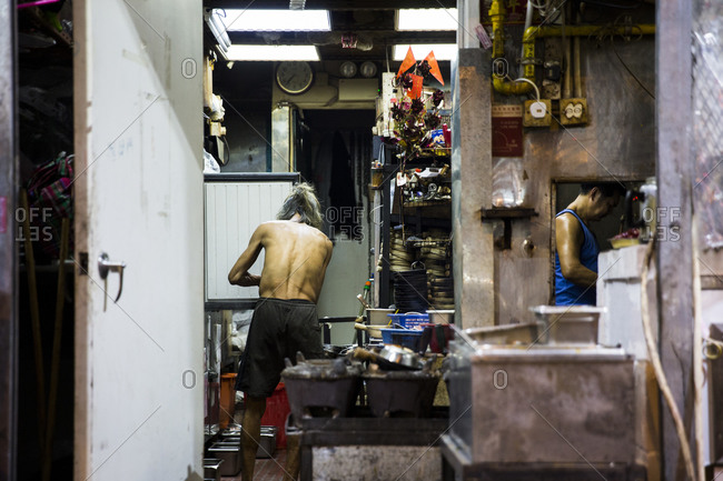 September 14, 2015: Men working in the kitchen of a street restaurant in Kowloon, Hong Kong