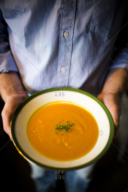 A man holds a bowl of freshly made soup made from organic squashes