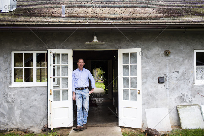 Seattle, Washington - November 14, 2013: Man standing in the doorway of his kitchen on a small island near Seattle, Washington