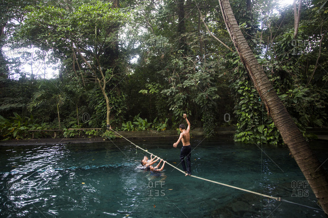 Nicaragua - December 11, 2015: Young boys enjoying a slackline above a natural spring pool on Ometepe Island in Nicaragua