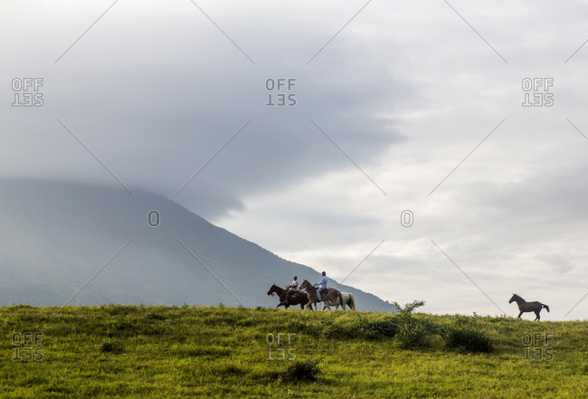 Two people riding horses in the rural countryside of Nicaragua