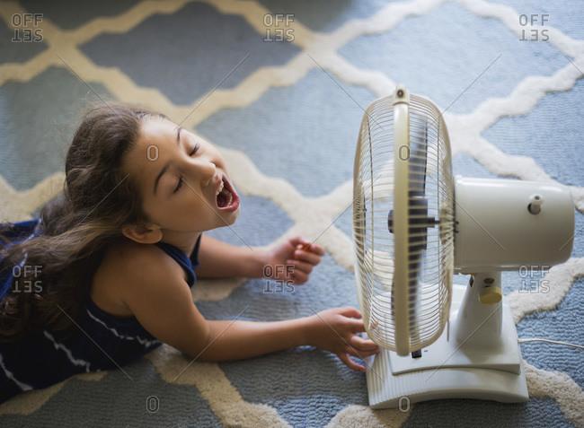 Girl lying in front of fan