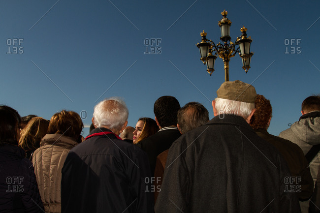 Madrid, Spain - November 5, 2014: Crowd of people next to a lamp post