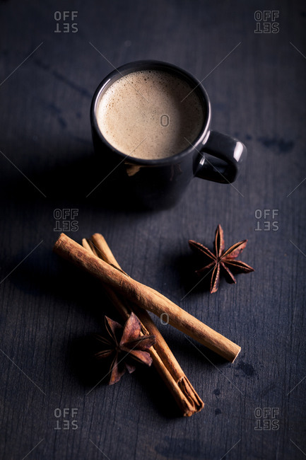 Overhead view of frothy coffee beverage with cinnamon stick and star anise
