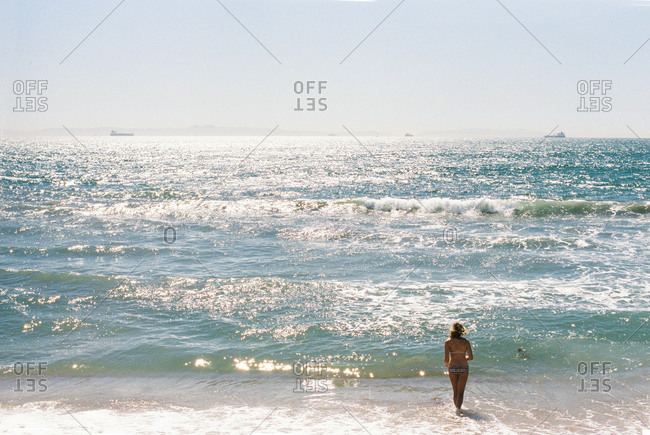 Woman wading into the ocean