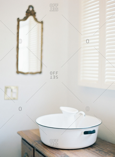 Pitcher and wash basin on wooden vanity
